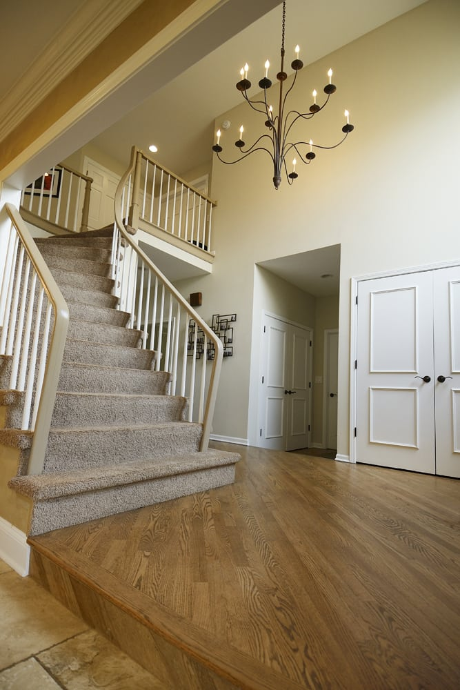 Wide angle photo of the front foyer of suburban house in Highland Park, IL with hard wood floors, carpeted stairway and wire chandelier Corporate Photography Architectural Photography