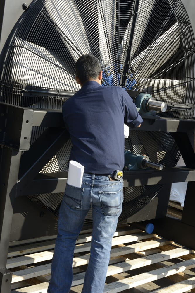 A blue shirted worker adjusting a giant fan in machine from the back