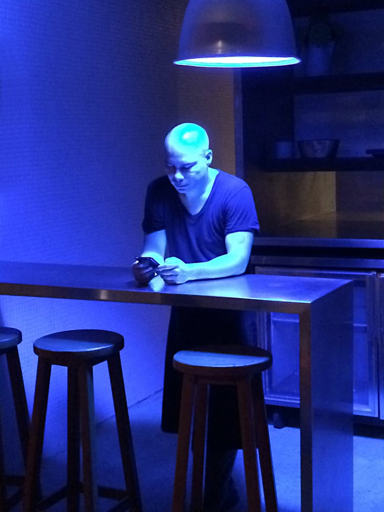 Blue light illuminating bald man looking at cell phone leaning on table