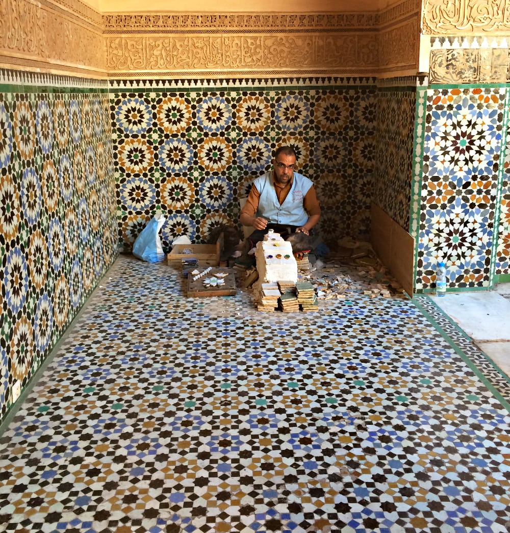 Male worker sitting on floor of ornately tiled room while working on mosaic tiles in Marrakesh, Morocco Corporate Photography Architectural Photography