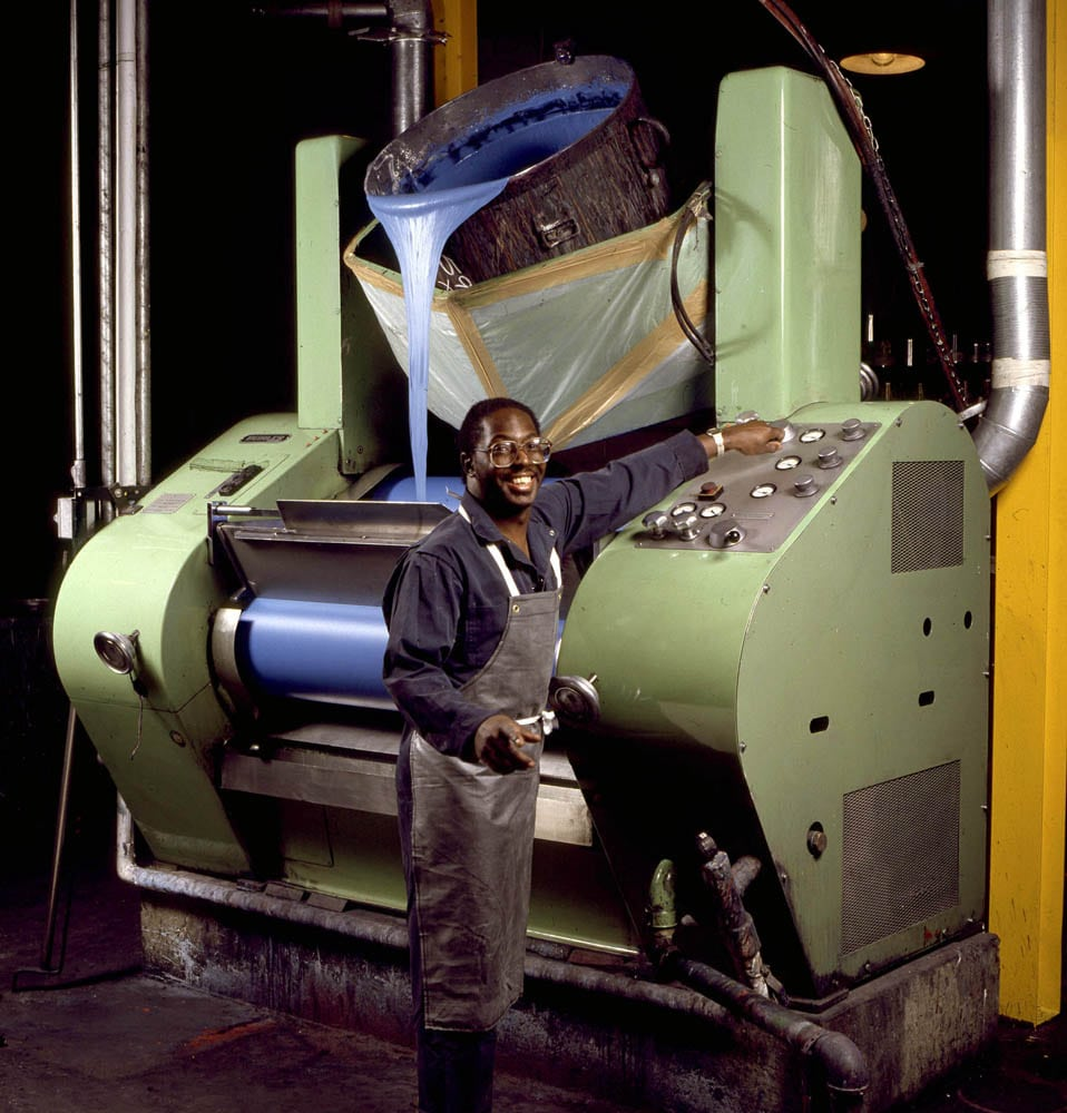 Worker smiling at camera while adjusting knob on large green paint crushing machine pouring blue paint into rollers