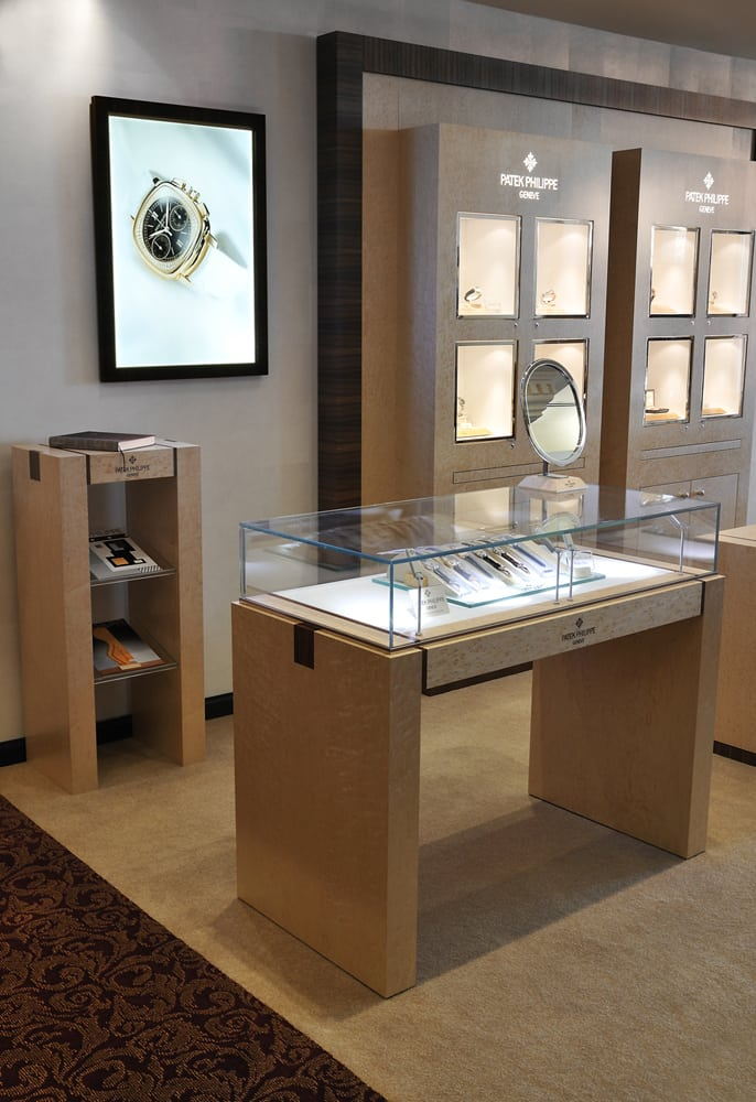 Angle view of Jewelry store area with light wood tables and chairs featuring high end watches. Detail on one table with round mirror Architectural Photography