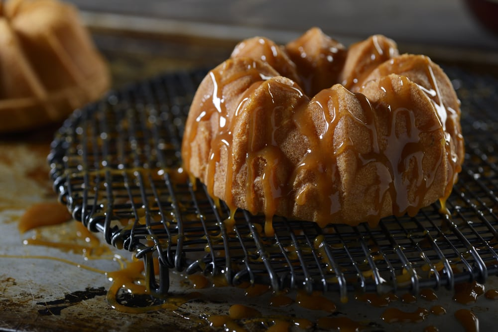 Close up shot of a nice bundt cake with caramel drizzled over it on black drain grid with another cake in background Product Photography