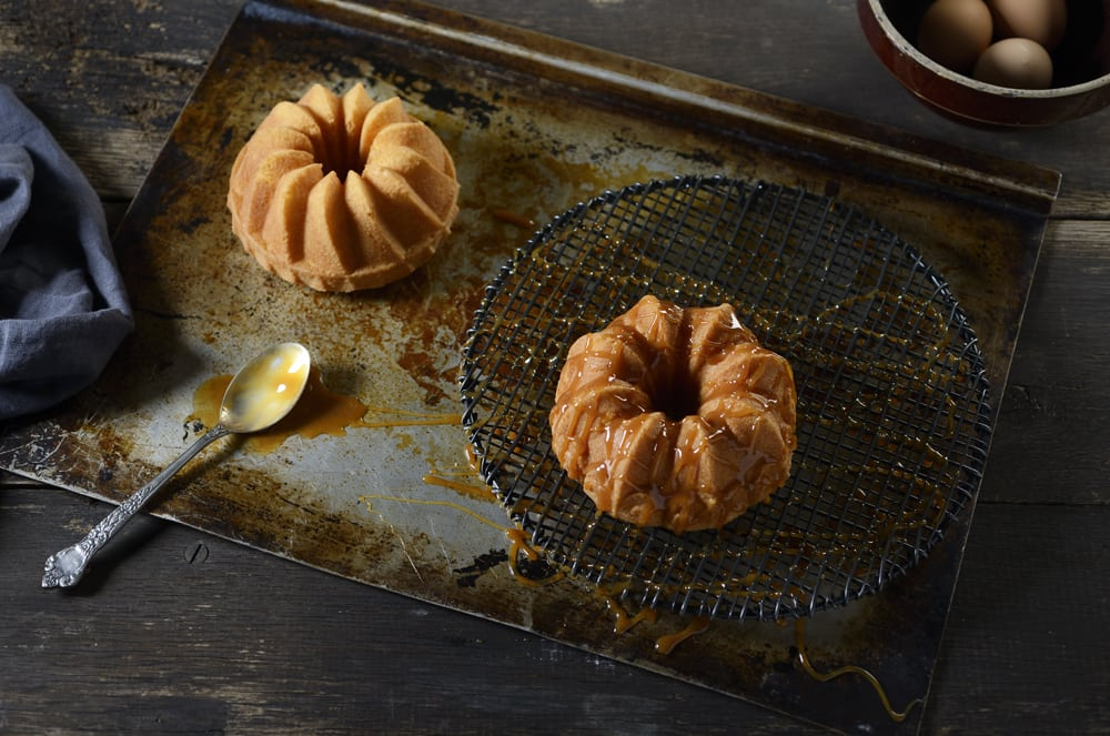 A top view of two bundt cakes with one sitting on black drain grid with caramel drizzled on it. Spoon on left with caramel in it. Bowl of eggs at top right Product Photography