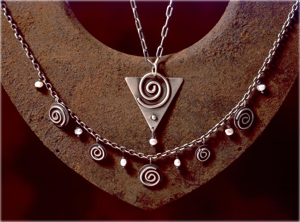 Spiral design silver necklaces displayed on rusty background Product Photography