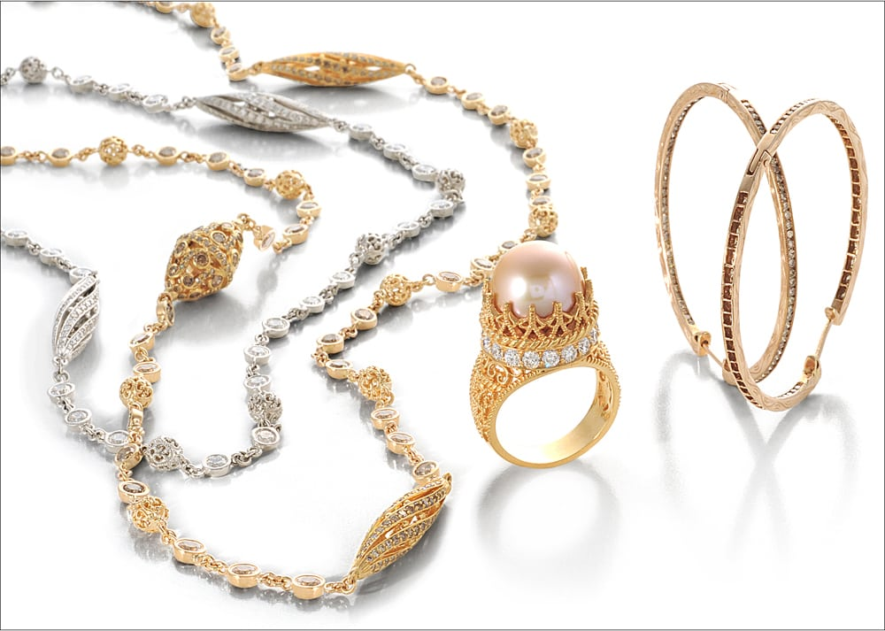 Ornate gold and silver jewelry collection on white background. Silver and diamond necklace, gold and diamond necklace, gold ring with diamond circling crown mount featuring large pink pearl and two gold bangles with brown diamonds.