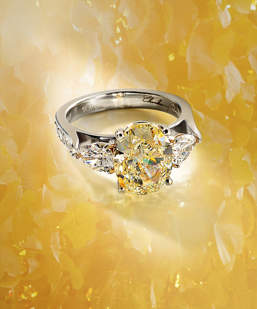 Large oval yellow diamond ring with 18K band and two pear shaped diamonds all on floral looking yellow background Product Photography