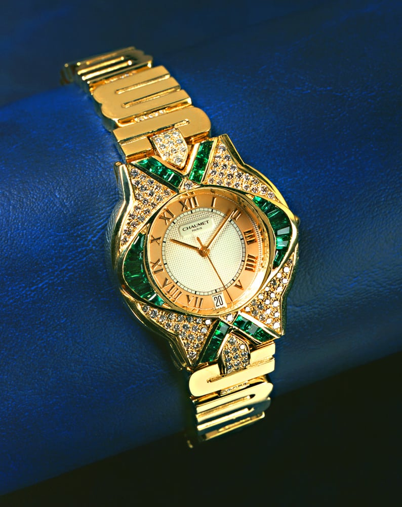 Fancy Chaumet men's watch with diamonds and emeralds and Roman Numerals on face. Band features stylized letters in gold all on blue vinyl background Product Photography
