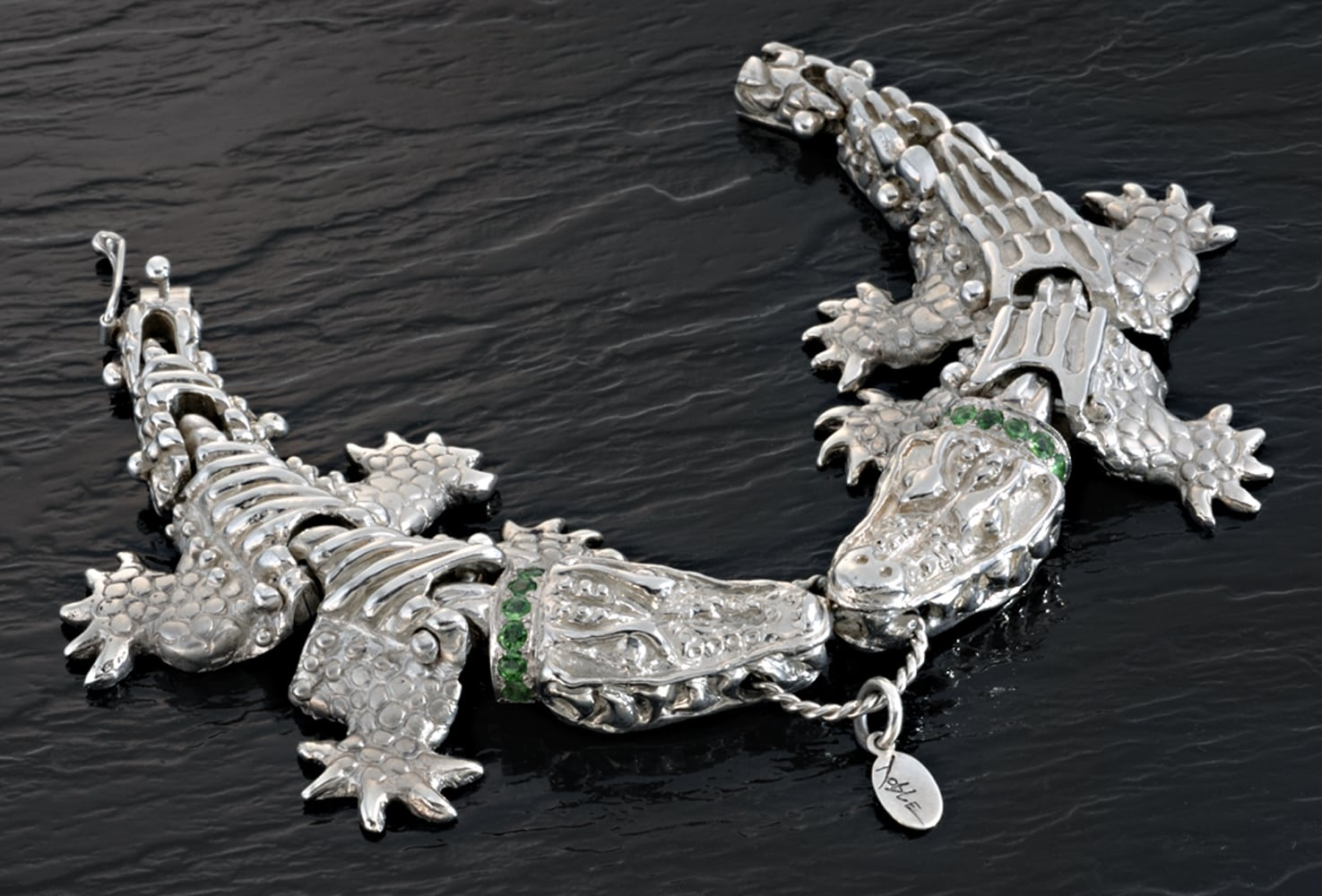 Silver Alligator bracelet with two alligators biting center ring. Alligators have collars with emeralds all on shiny black patterned background Product Photography