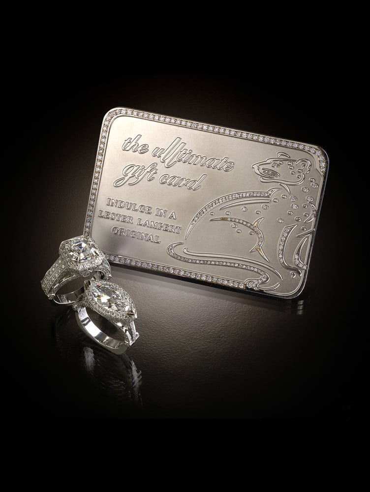 "Product shot featuring dramatically lit platinum and diamond gift card with the inscription ""the ultimate gift card"" and a leopard shape all with two diamond rings in foreground on black background Product Photography"