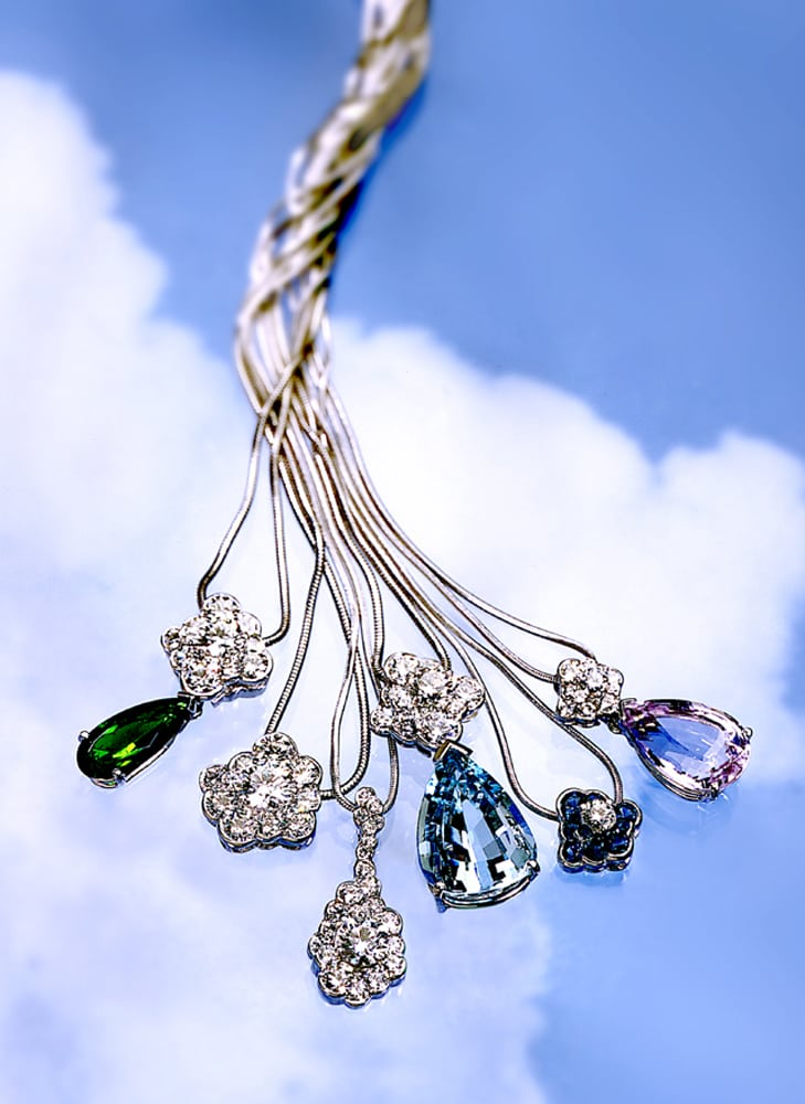 Six pendants on silver chains three with large colored stones and others with diamonds on blue sky and clouds background. Chains are all twisted up above the pendants.