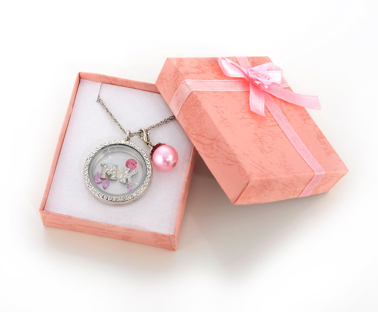 "Small Pink gift box with pink ribbon opened holding a silver pendant with letters ""M"" and ""K"" inside glass and a pink pearl all on a silver chain. Product Photography"