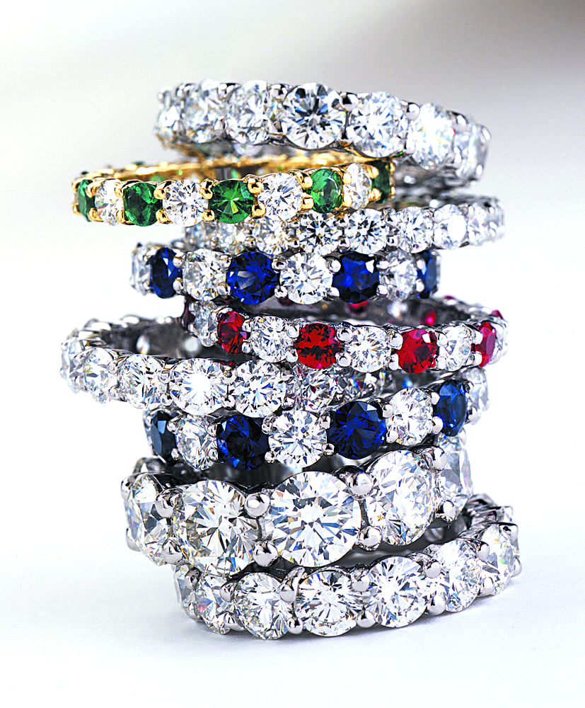 Stack of nine diamond ring, all encircled with large diamonds, one with emeralds, one with rubies and two with sapphires. Product Photography