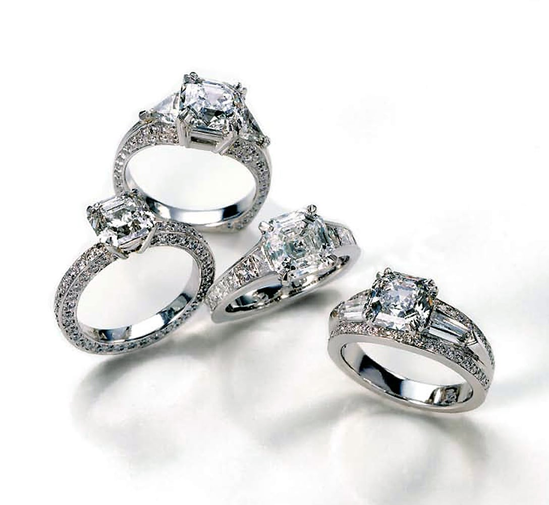 Four diamond ring arrangement with platinum settings and all with emerald cut diamonds viewed from above on white background