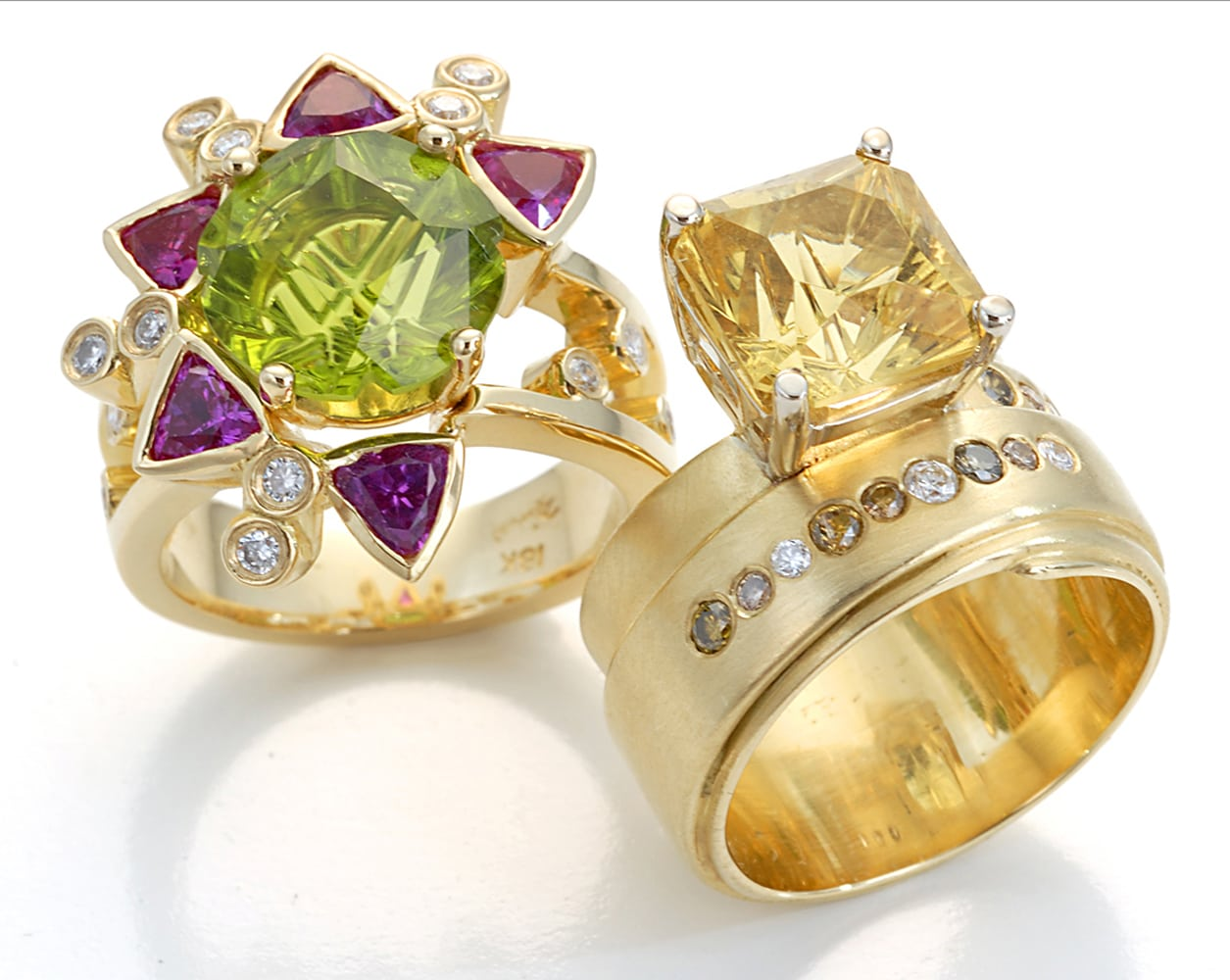 two gold rings standing together. the left one with a star pattern made of a large green stone surrounded by purple stones and diamonds sprinkled. The right one has a large yellow radiant cut stone with brown and white diamonds embedded on band Product Photography