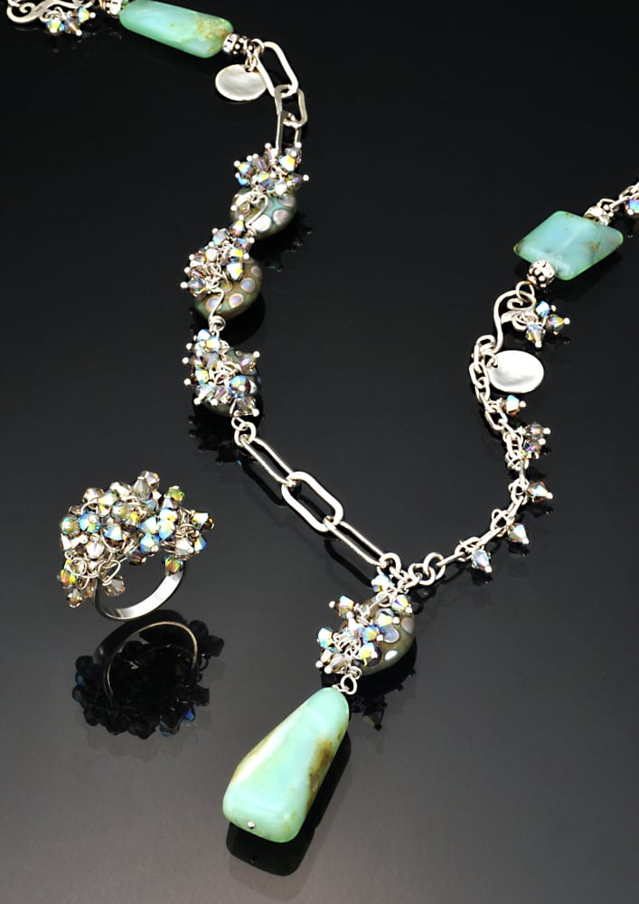 Necklace and ring set of silver links with rainbow stones and the necklace has blue polished stones