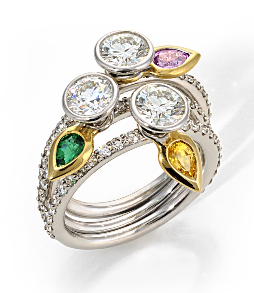 platinum ring stacking set of three rings, all with large round diamonds on top and spinning gold 'leaves' on each, one with an emerald, one with topaz and one with pink diamond. Product Photography