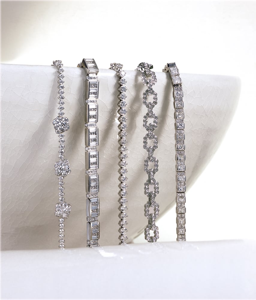 five diamond tennis bracelets spilling over edge of a white bowl