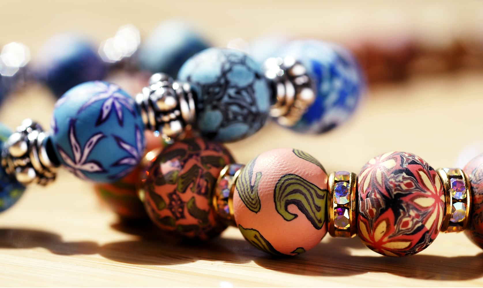 Hand made beads with intricate designs on two bracelets. One orange beads and one with blue beads piled on top