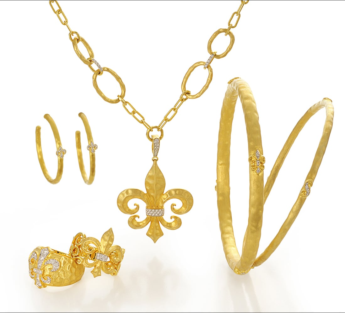 Arrangement of six 18k gold pieces, one large link chain with a flour de lis gold and diamond pendant, gold hoop earrings with diamonds, two gold rings with flour de lis designs and two gold bangles with small diamond flour de lis designs