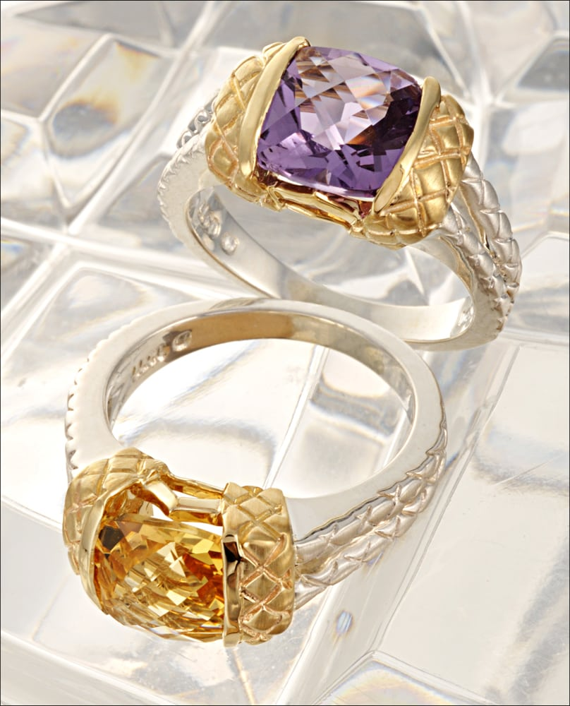 Two white and yellow gold rings, one lying dow and the other standing, with a large purple stone and a large yellow stone