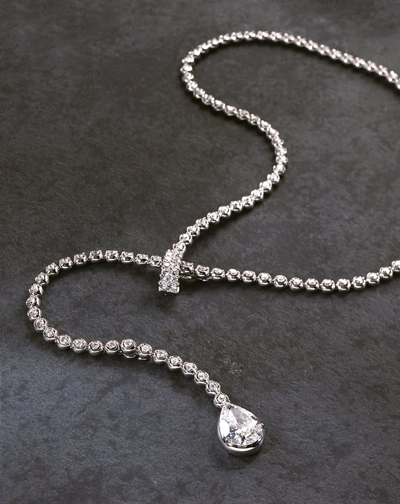 String of diamond adjustable necklace with large pear shaped diamond on end, all on gray slate background