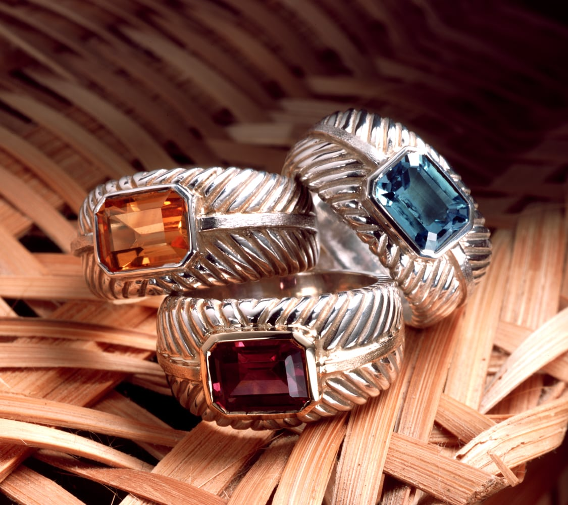Three silver rings with a wicker pattern and yellow, blue and red stones, stacked on a wicker background
