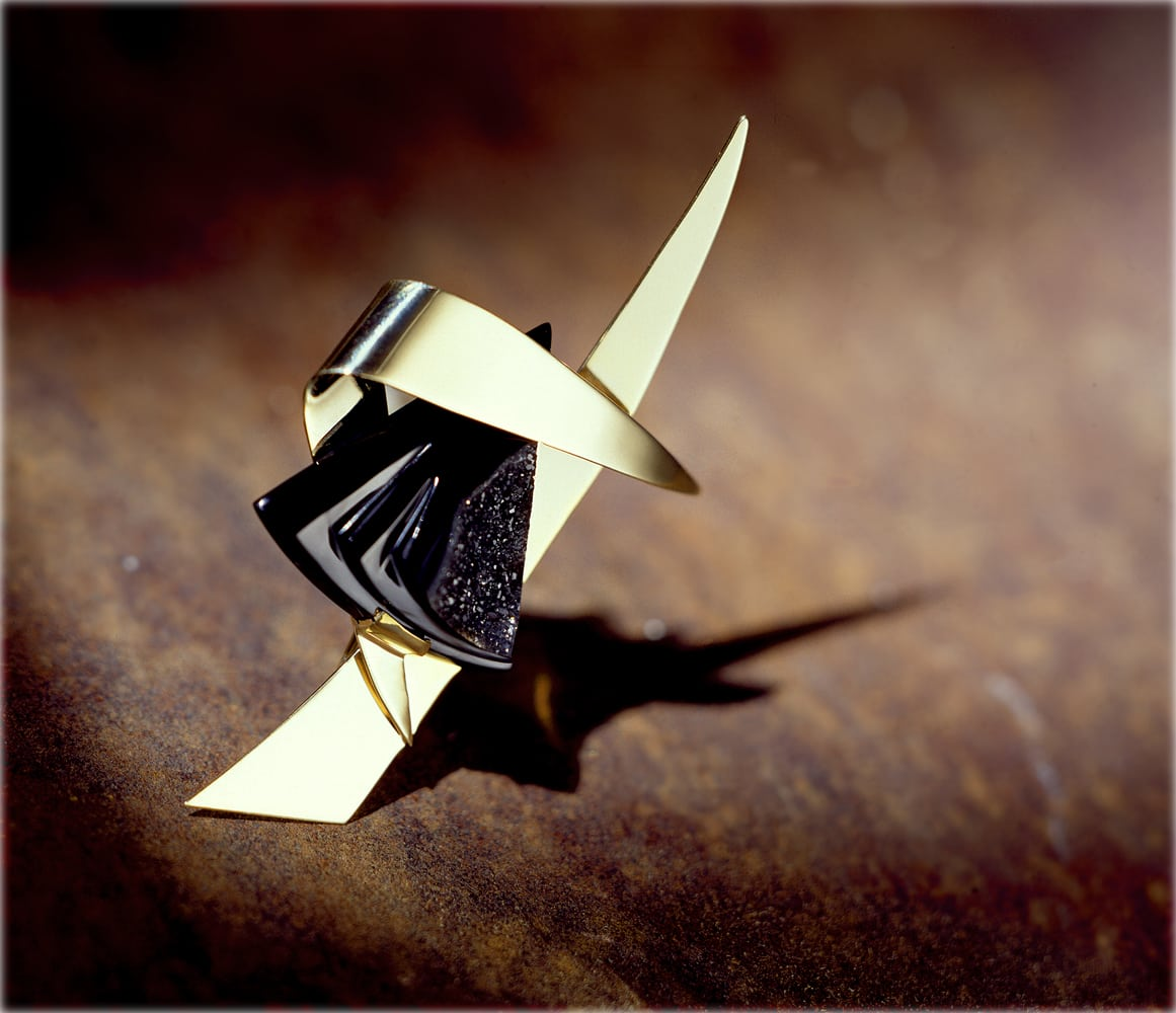 Angular gold and black onyx pin with strong shadow on rusty metal background