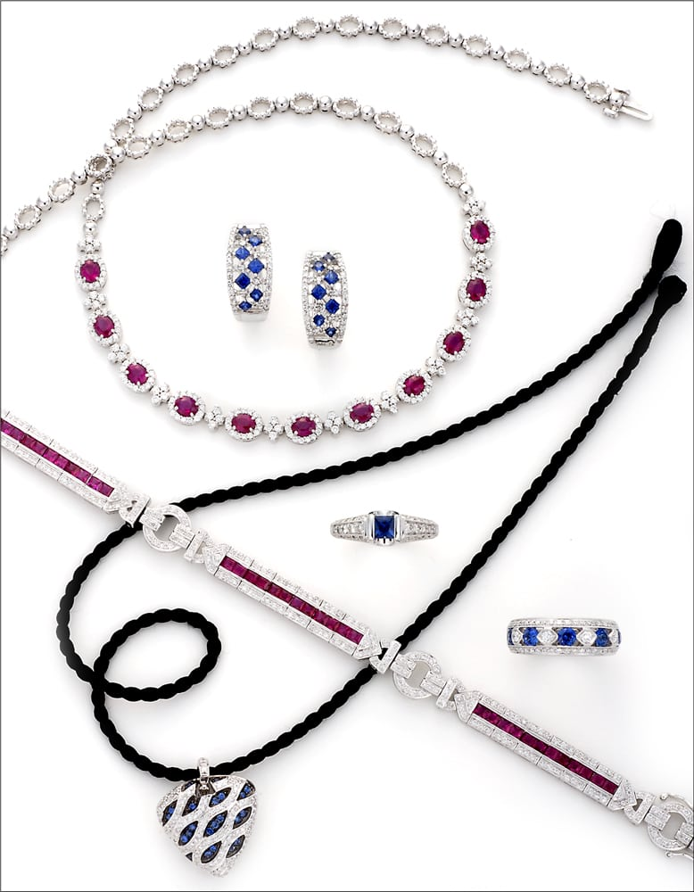 Design Arrangement of ruby necklace, Diamond and ruby bracelet, Sapphire and diamond heart pendant on black cord, and four sapphire and diamond rings on white background