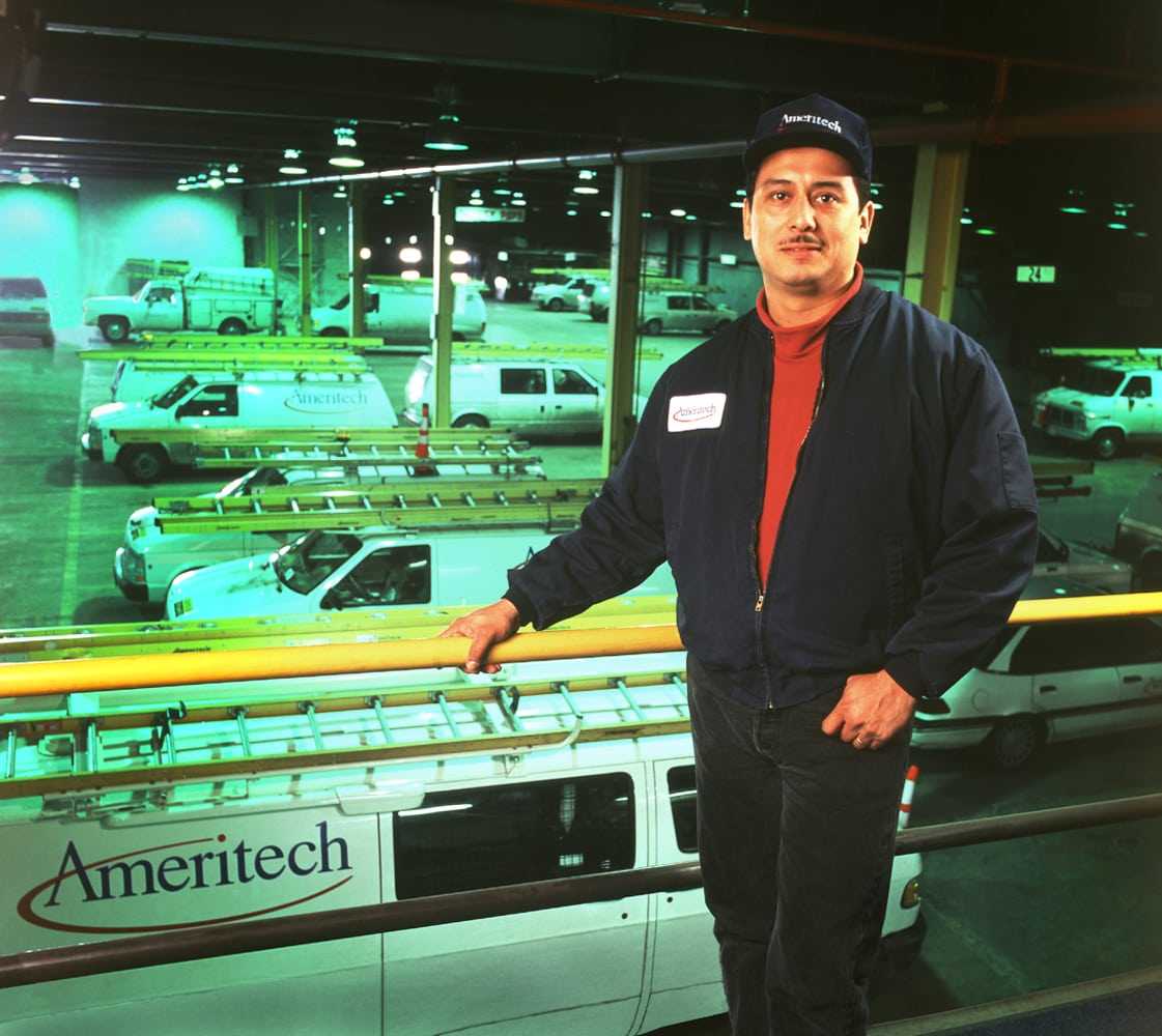 Ameritech worker leaning on yellow railing in front of large garage with Ameritech utility trucks with ladders on roofs Corporate Photography