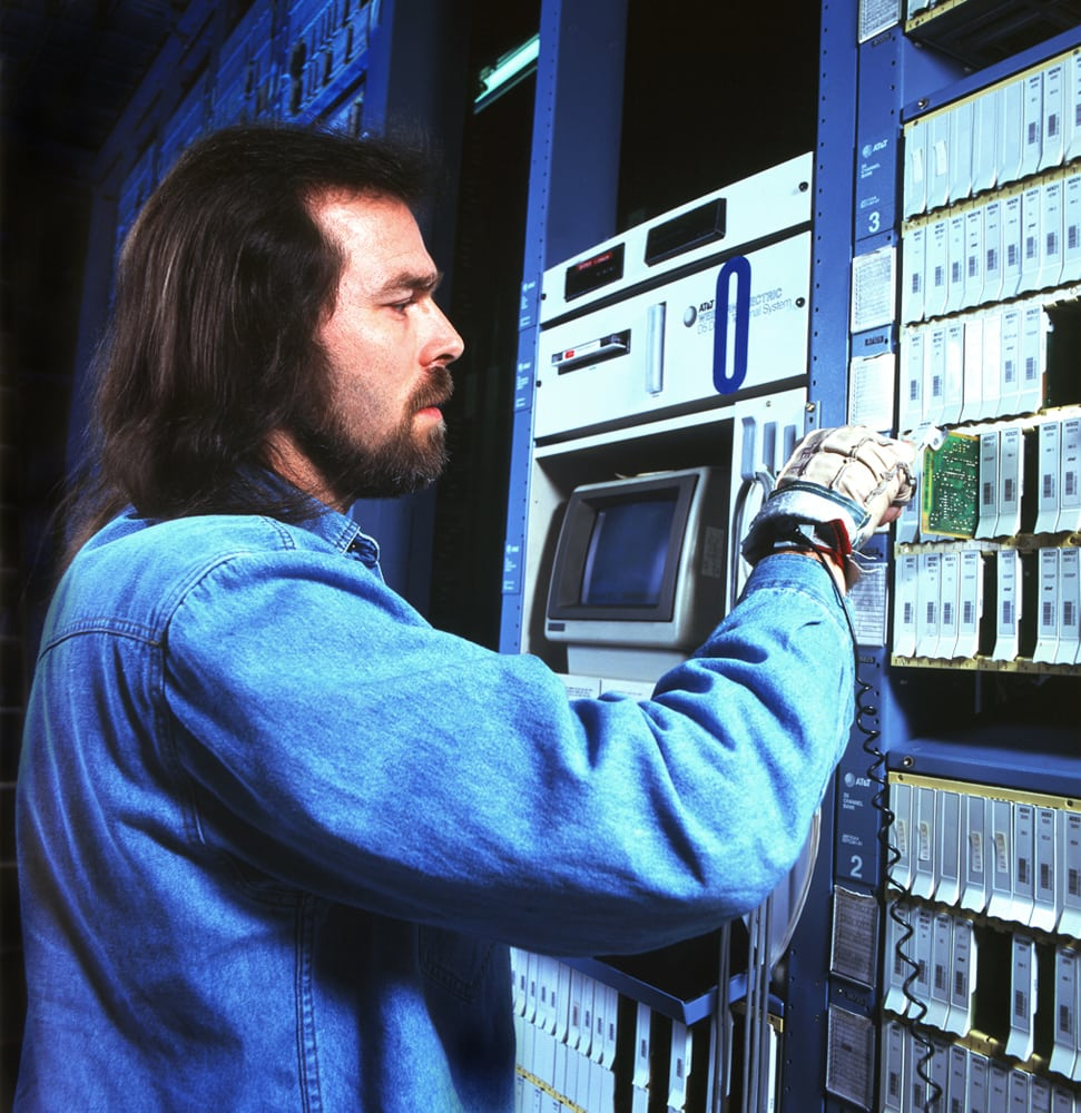 IT worker in denim shirt placing a circuit board into a rack of servers Corporate Photography