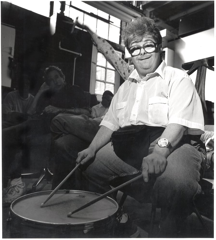 Black and white photo of large guy with big glasses holding drum sticks on snare drum Corporate Photography