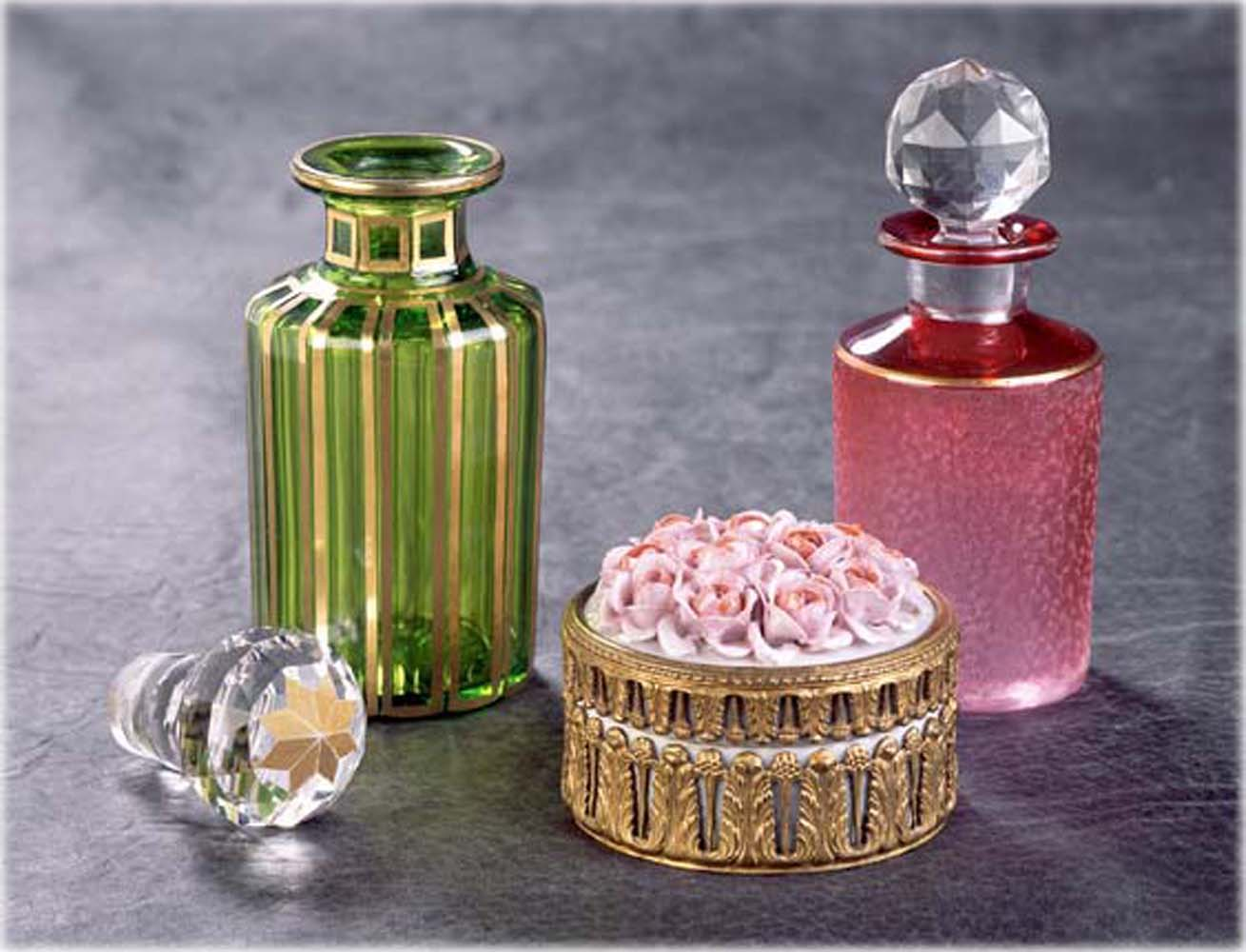 Vintage Green and Pink Perfume bottles and gold round powder puff box with sculpted rose top on gray textured background Product Photography
