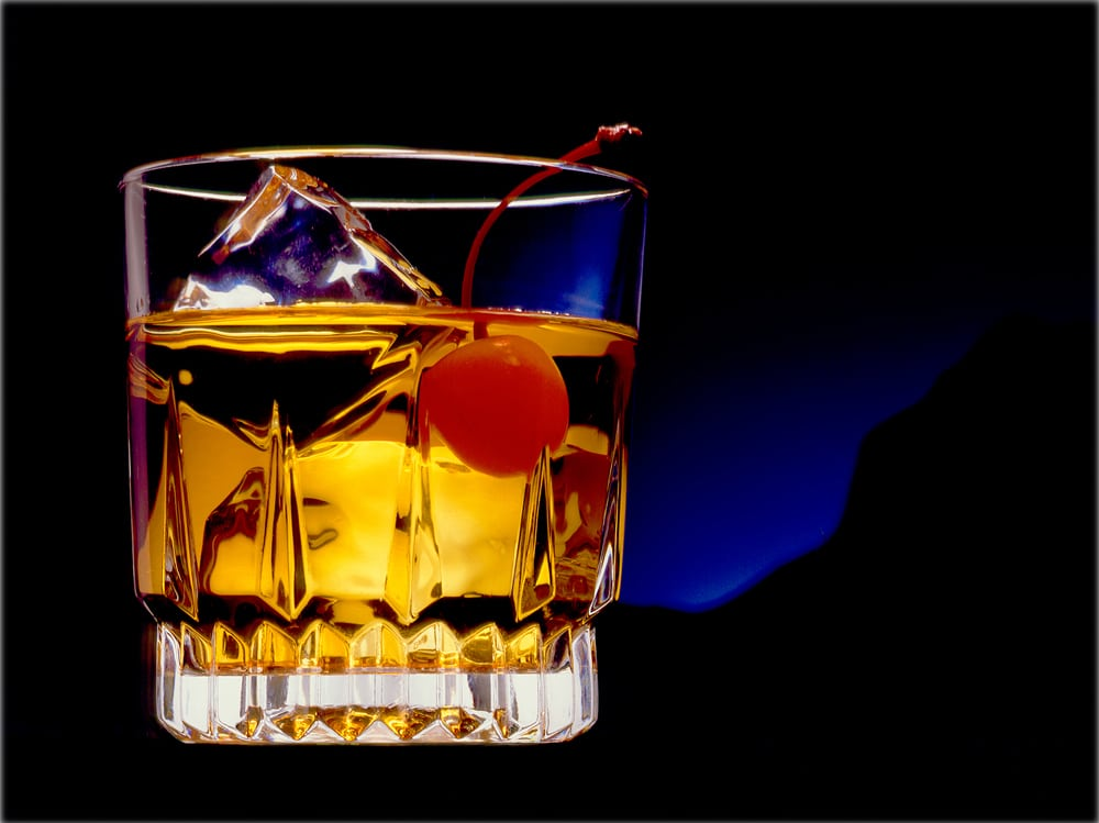 Rock glass holding Manhattan drink, ice cubes and cherry on black background with blue mountain silhouette Product Photography