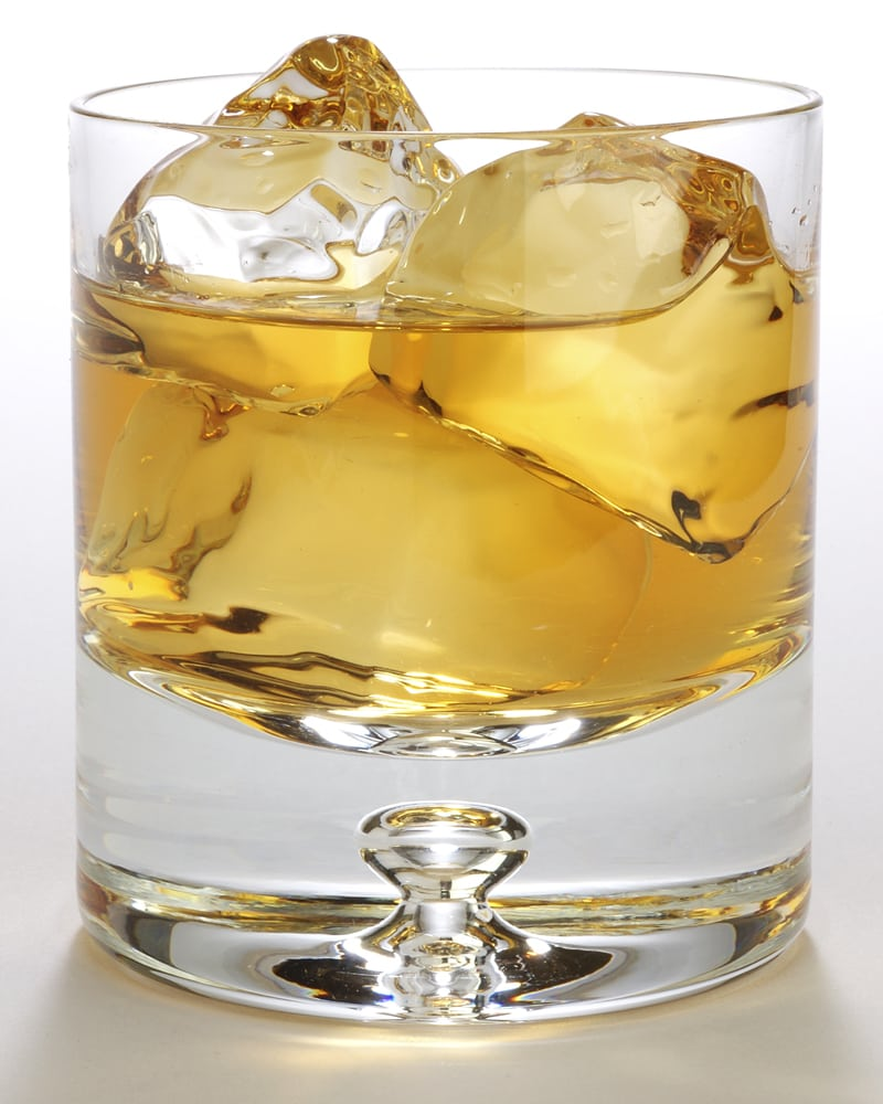 Solid looking glass rock glass holding ice cubes and whisky drink on white background Product Photography