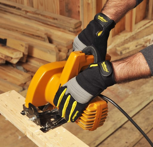 Action shot of yellow power saw cutting board with gloved hands holding it Product Photography