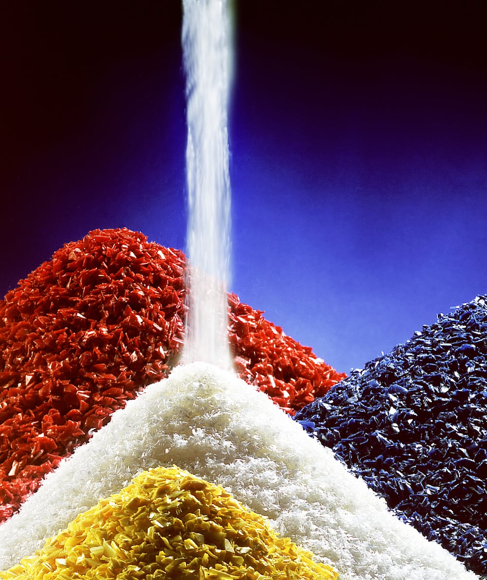 Piles of plastic chips in red, blue yellow and white colors on blue background with white color spilling onto pile