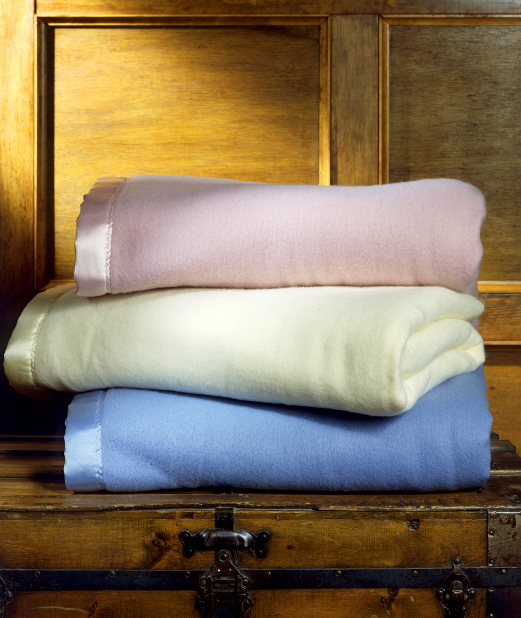 Stack of three fuzzy baby blankets in pink, yellow and blue on top of a chest with wood panel background Product Photography