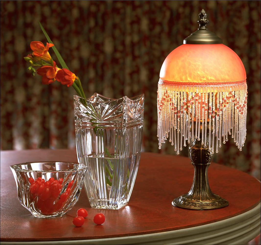 Crystal bowl, crystal vase and vintage colored glass and brass lamp sitting on red table with red curtain background Product Photography