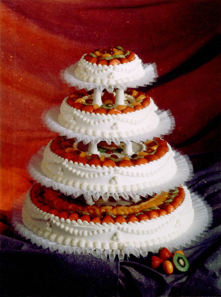 Four tier white wedding cake with colorful fruit topping every layer on gray fabric backdrop and red glow in back Product Photography