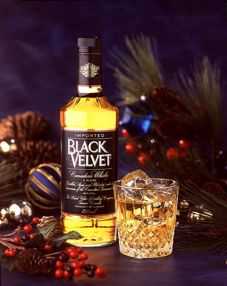 Product shot of Black Velvet Canadian Whisky with a fancy cut glass rock glass with whisky and ice cubes in a Christmas holiday setting with pine needles, ornaments and red berries Product Photography