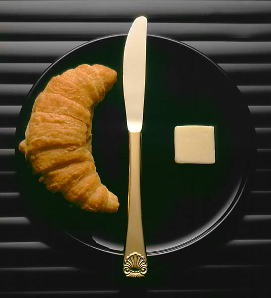 Round black plate holding a gold butter knife down the center, square of butter on right, and browned croissant on left Product Photography