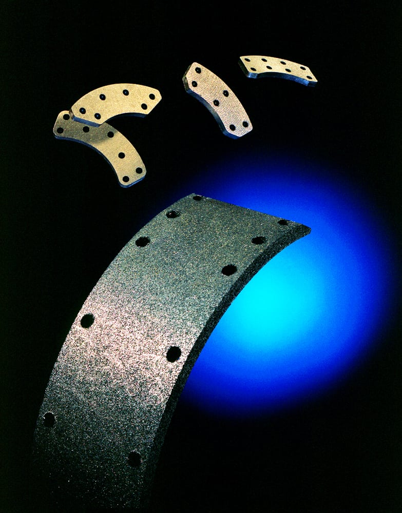 Photo of a feature brake pad up front with four additional brake pads 'floating' behind and blue glow background Product Photography