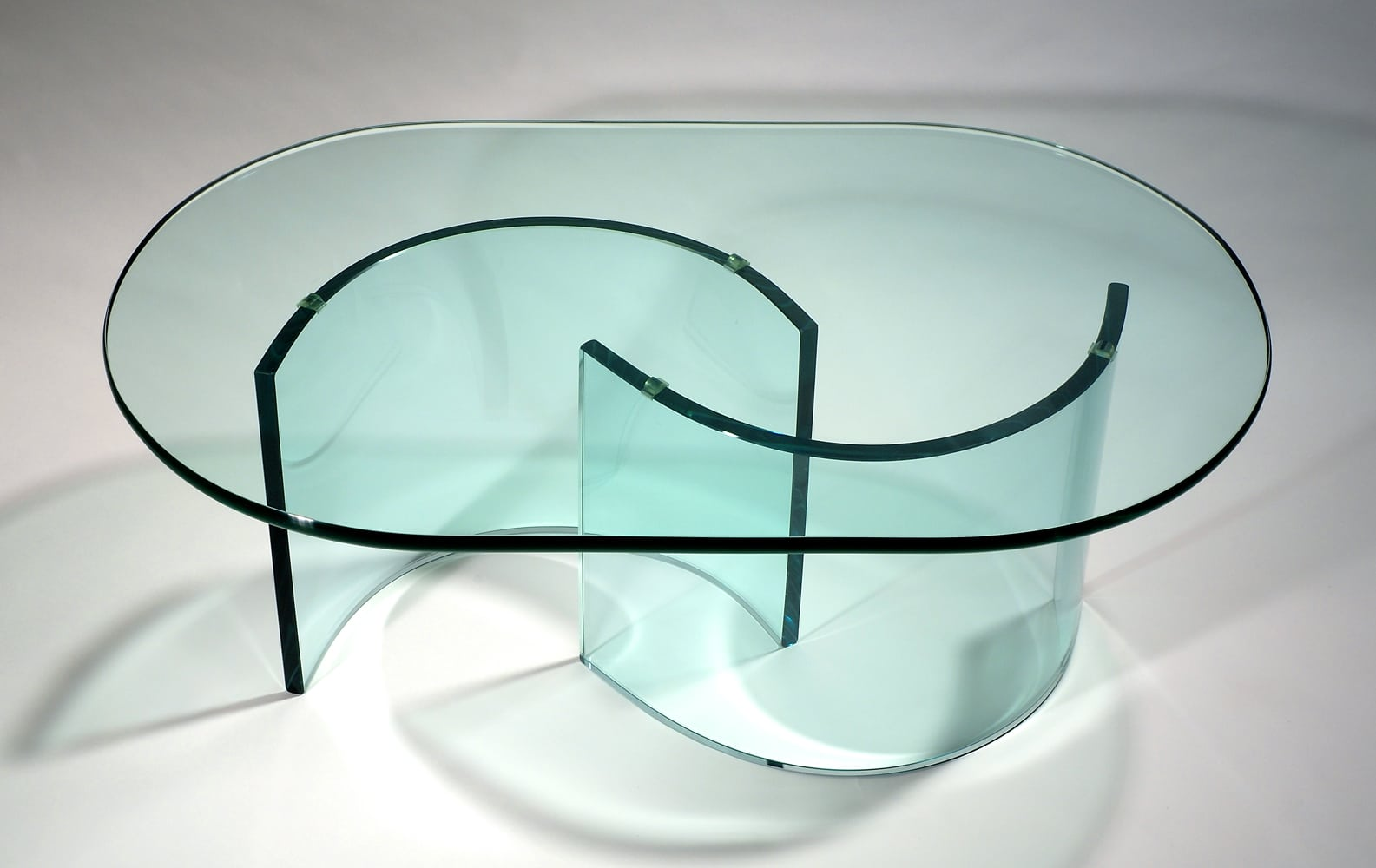 Oval Blue glass table with half circle legs with light shining through onto white background Product Photography