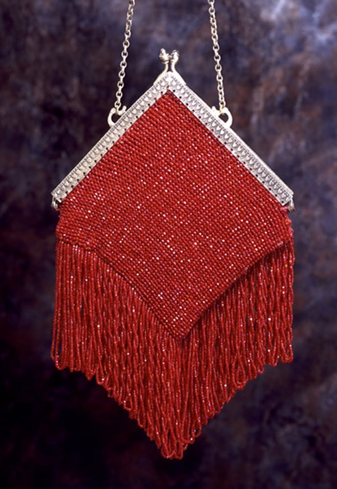 Vintage red clutch purse with red fringe and silver clasp and chain hanging with brown and gray mottled background Product Photography