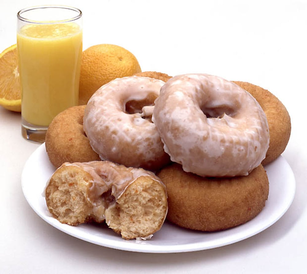 Stack of glazed doughnuts sitting on white plate with oranges and glass of orange juice behind Product Photography