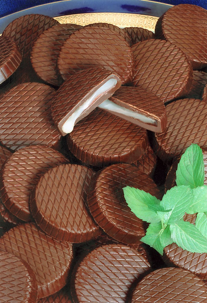 Plate of chocolate Peppermint Patties with one cut in half with permit filling dripping out. Peppermint leaves as garnish in front Product Photography