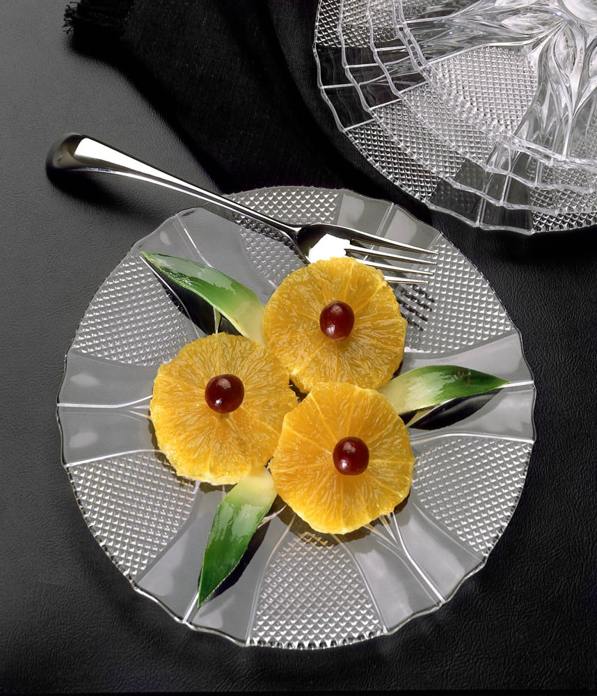 Fruit display on glass plate featuring three orange slices with grapes in centers Product Photography