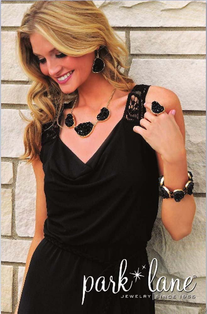 """Model shot of blonde woman in black dress wearing bulky black stone jewelry set of necklace, earrings, ring and bracelet standing in front of stone wall with logo """"park lane"""" in bottom right Jewelry Photography"""