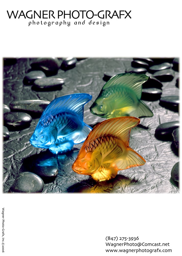 Ad for Wagner Photo-Grafx featuring Arrangement of three Swarovski crystal fish, one blue, one green and one orange on black textured background and gray pebble props Product Photography